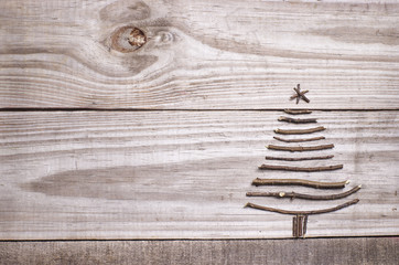 Christmas tree arranged from sticks, wooden grey background