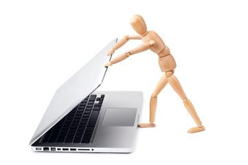 Wooden man closes a laptop