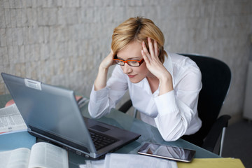 Stressed blonde businesswoman with laptop
