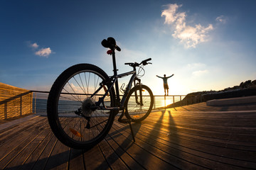 silhouette of sportsman and his mountain bike at the sunset
