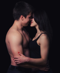 Beautiful young couple hugging and kissing isolated on black bac