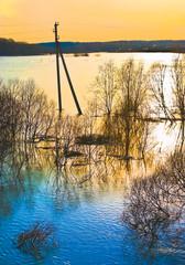 Orange sunset mirrored in spring flood