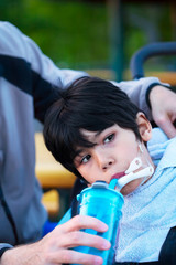 Disabled biracial little boy in wheelchair drinking water from s