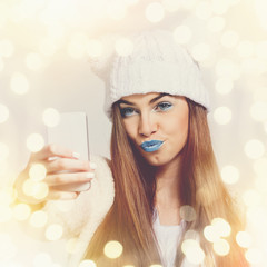 Young woman with beanie and blue lipstick taking a selfie