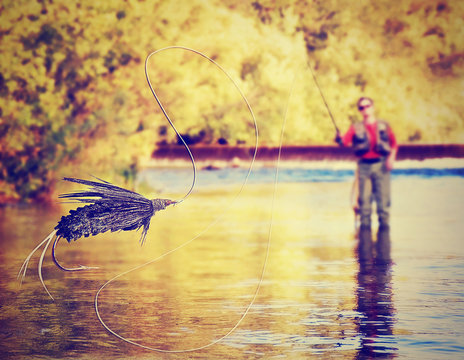 a person fly fishing with a big trout in front