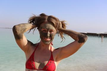 Beautiful girl mud mask in the Dead sea