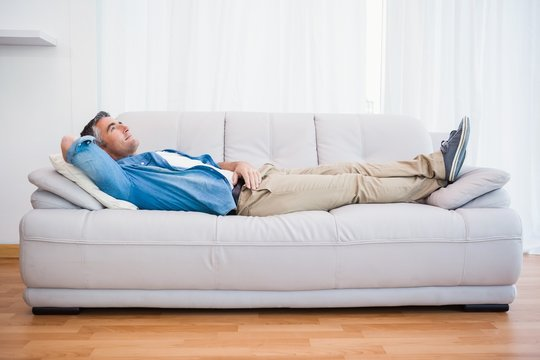Smiling man lying and relaxing on the couch