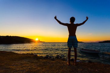 man at sunset standing with arms raised up above
