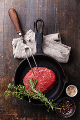Raw meat Ribeye steak, seasonings and meat fork on cast iron fry