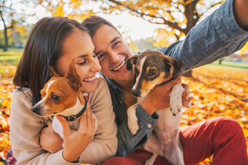 Smiling young couple with dogs outdoors in autumn park