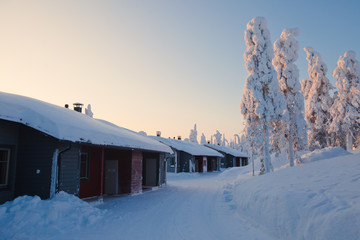 Beautiful lapland snowy winter landscape with cottage cabin vill