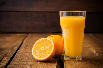 Poster Juice Orange fruit and glass of juice on brown wooden background