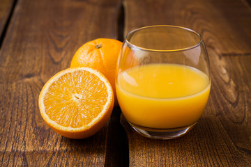 Orange fruit and glass of juice on dark wooden table