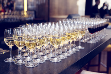 Glasses of white wine on bar counter, toned