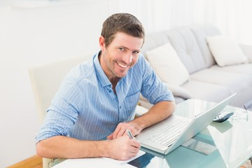Smiling businessman writing at his desk