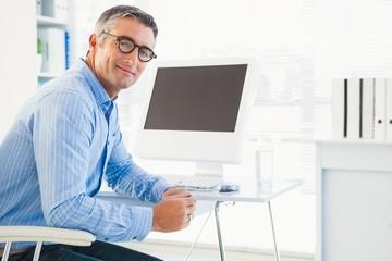 Smiling man with glasses at his desk looking at camera