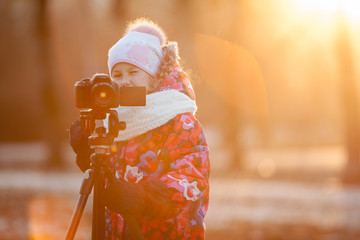 Young child taking pictures on camera using a tripod, copyspace