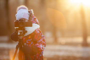 Child photographer takes pictures on camera using a tripod, sun