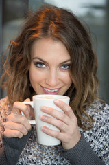 Pretty Brunette Drinking Coffee from a Mug