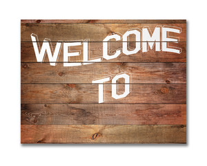 Vintage WELCOME sign on natural wooden surface.