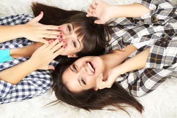Beautiful girls twins in pajamas lie on carpet