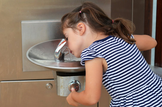 Child Drinking From Outdoor Water Fountain