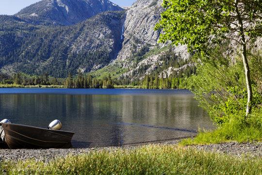 Aluminum Fishing Boat On Shore Of Mountain Lake