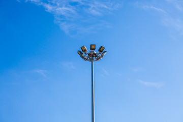 Lamp or sports lighting on tall lamppost with blue sky