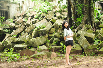 young girl standing before ancient rubbles, smiling at camera