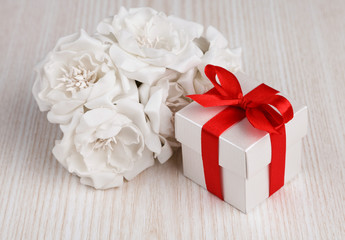 white flowers and gift box with red ribbon