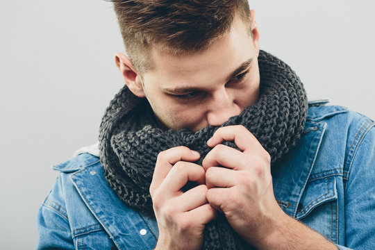 Thoughtful Handsome Man Smelling his Knitted Scarf