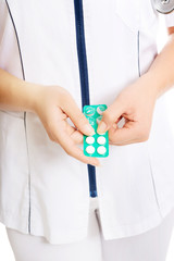 Close up on female doctor holding pills