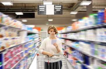 woman pushing cart looking at goods in supermarket
