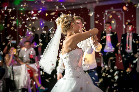 blonde bride dancing at restaurant in flying confetti