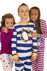 Three kids wearing winter pajamas two girls afraid