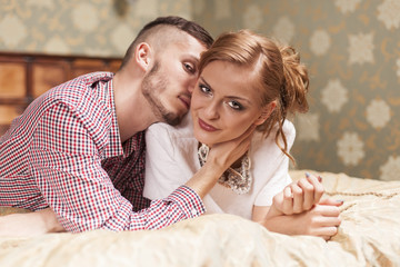 Young couple lying on the bed at hotel room