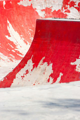 Old red skating ramp with half pipe rail.