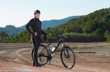 Cyclist standing with mountain bike in nature