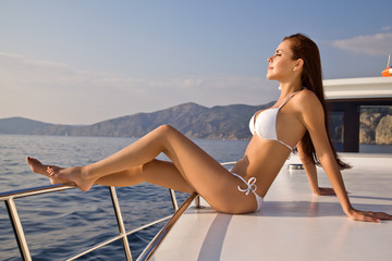 Beautiful girl sunbathing on a yacht