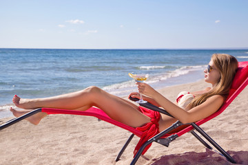 Girl with a cocktail martini on the beach