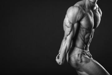 Handsome muscular guy, bodybuilder, posing on a black