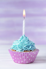 Delicious birthday cupcake on table on light purple background