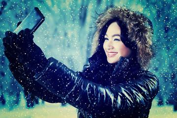 Girl in winter jacket taking self portrait