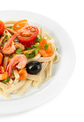 Tasty pasta with shrimps, black olives and tomatoes isolated