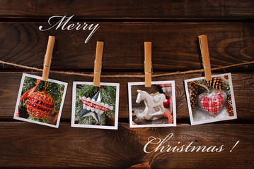 christmas photos hanging on rope against wooden background