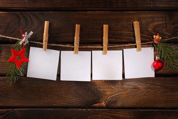 blank paper cards hanging on rope against wooden background