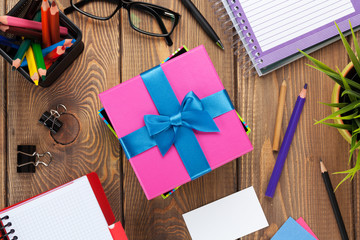 Gift box and office supplies over office table