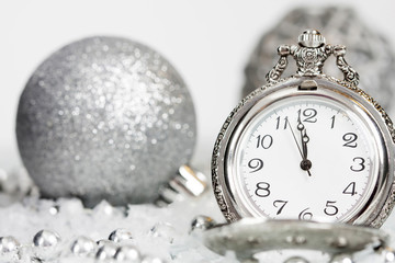 Old silver clock close to midnight and Christmas decorations
