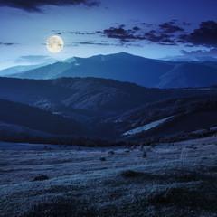 field on hillside near village at night