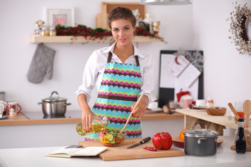 Smiling young woman  mixing fresh salad